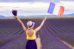 Femme avec le drapeau français dans le domaine de lavande Photo stock