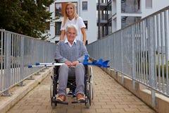 Femme avec le fauteuil roulant sur le rampe image libre de droits