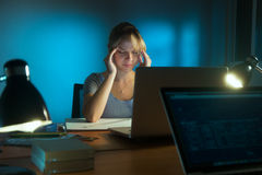 Femme avec le fonctionnement fatigué par yeux tard la nuit dans le bureau Photo stock