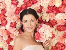 Femme avec le fond plein des roses photo stock
