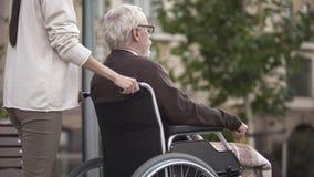 Femme avec le grand-père handicapé dans le fauteuil roulant marchant en parc, offrant images libres de droits