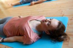 Femme avec le groupe de personnes faisant le yoga au studio Photo stock