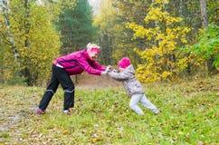 Femme avec le jeu de fille en parc d'automne Photo stock