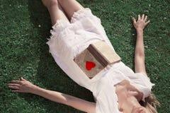 Femme avec le livre d'amour dans le pré ensoleillé Photographie stock libre de droits