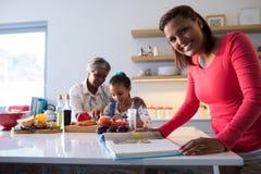 Femme avec le livre de cuisine se tenant dans la cuisine Photo stock