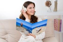 Femme avec le livre de photo écoutant un coquillage Photo stock