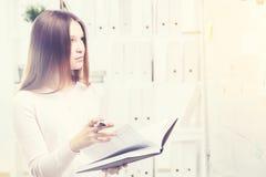 Femme avec le livre regardant des graphiques de gestion Images stock