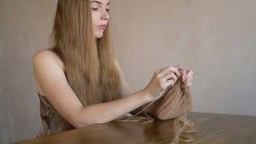 Femme avec le long tricotage de cheveux blonds banque de vidéos