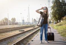 Femme avec le luggadge attendant sur la gare ferroviaire le train le jour ensoleillé photographie stock libre de droits