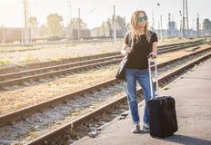 Femme avec le luggadge attendant sur la gare ferroviaire le train le jour ensoleillé image libre de droits