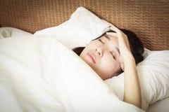 Femme avec le mal de tête se trouvant sur le lit Image libre de droits