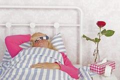 Femme avec le mal de tête se situant dans le lit Image stock