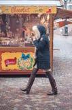 Femme avec le manteau d'hiver marchant devant la boutique de pain d'épices au marché de Noël Image libre de droits