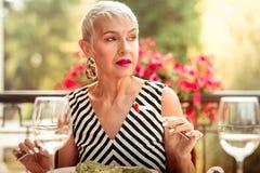 Femme avec le maquillage gentil mangeant de la salade pour le dîner dehors photo libre de droits