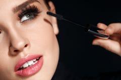 Femme avec le maquillage, longs cils appliquant le mascara Faire le maquillage Photos libres de droits