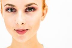 Femme avec le maquillage naturel sur un sourire léger de fond Image stock