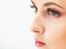 Femme avec le maquillage naturel sur un sourire léger de fond Photographie stock