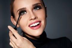 Femme avec le maquillage parfait, longs cils noirs appliquant le mascara Image stock