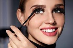 Femme avec le maquillage parfait, longs cils noirs appliquant le mascara Images libres de droits
