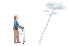 Femme avec le marcheur se tenant devant l'échelle Image libre de droits