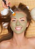Femme avec le masque de massage facial d'argile image stock
