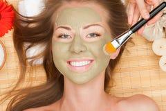 Femme avec le masque de massage facial d'argile Image libre de droits