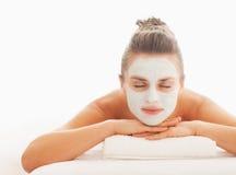 Femme avec le masque de revitalisation sur le visage s'étendant sur la table de massage Images stock