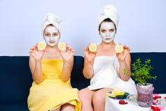 Femme avec le masque facial affichant le citron de parts Photographie stock libre de droits