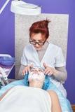 Femme avec le masque facial au salon de beauté image libre de droits