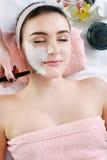Femme avec le masque facial d'argile dans la station thermale de beauté Photos stock