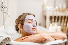 Femme avec le masque facial dans la salle de bains photographie stock