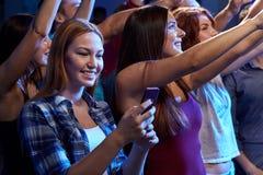 Femme avec le message textuel de smartphone au concert Photographie stock libre de droits