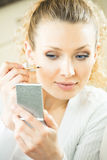 Femme avec le miroir effectuant le visage photographie stock