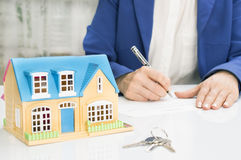 Femme avec le modèle de maison et le document de signature de contrat de stylo Image stock