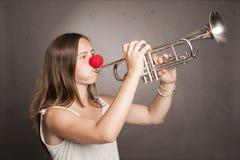 Femme avec le nez rouge jouant la trompette photo libre de droits