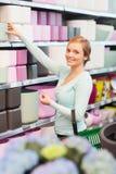 Femme avec le panier à provisions choisissant le pot de fleurs Photos stock