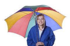 Femme avec le parapluie dans une couche de pluie bleue Photos stock