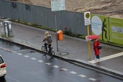 Femme avec le parapluie pendant pleuvoir la rue humide de jour, projet de construction dans le fischerinsel Image stock