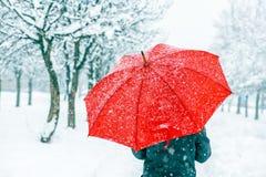Femme avec le parapluie rouge dans la neige photographie stock