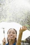 Femme avec le parapluie sous la pluie Photo stock