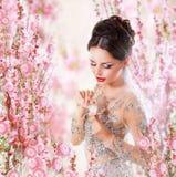 Femme avec le parfum au-dessus du fond floral Photos stock