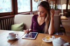 Femme avec le PC de comprimé utilisant l'Internet dans le restaurant images stock