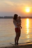 Femme avec le petit bébé par l'eau Photos stock