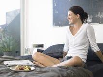 Femme avec le petit déjeuner et le journal sur le lit Image stock