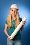 Femme avec le plan de casque et de construction de constructeur heureux de faire Photo libre de droits
