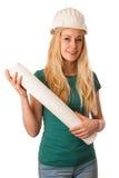 Femme avec le plan de casque et de construction de constructeur heureux de faire Images libres de droits
