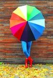 Femme avec le port coloré de parapluie bottes en caoutchouc rouges dans le jour d'automne au-dessus du fond en bois Image stock