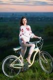 Femme avec le rétro vélo sur la colline le soir image stock