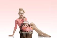 Femme avec le regard créatif et le petit gâteau Photo stock