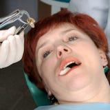 Femme avec le regard ouvert de bouche sur sa dent d'extrait Images libres de droits